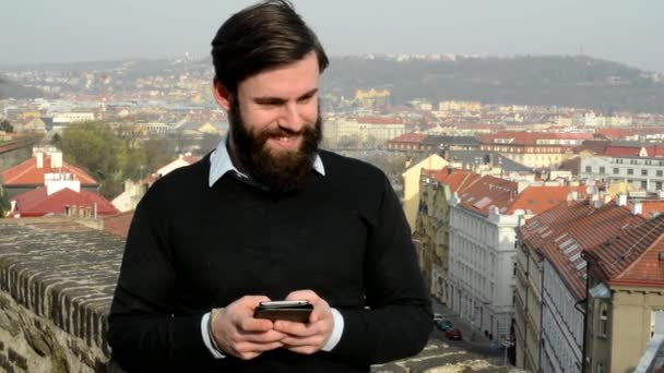 young handsome man with full-beard (hipster) works on mobile phone and smiles - city in background