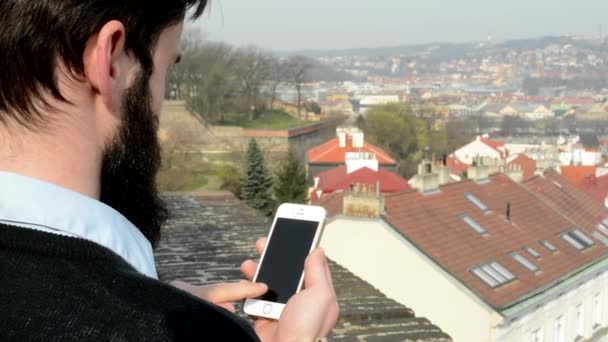 young handsome man with full-beard (hipster) works on mobile phone (smartphone) - city in background