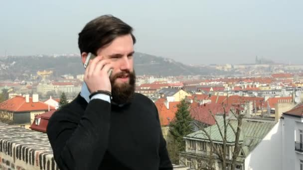 young handsome man with full-beard (hipster) walking and phone with smartphone - city in background