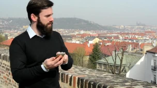 young handsome man with full-beard (hipster) walking and works on mobile phone (smartphone) - city in background (buildings - roof)