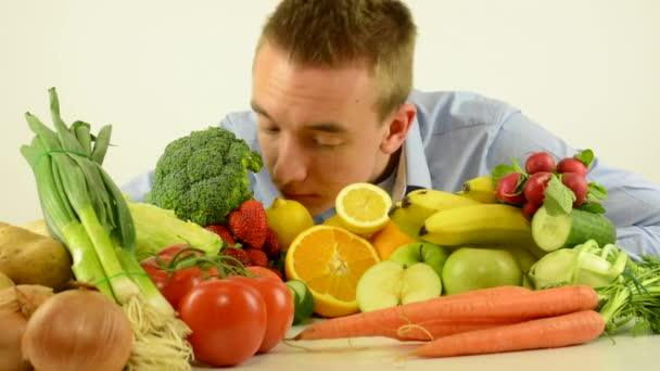 man smells to healthy food - vegetables and fruits - white background studio