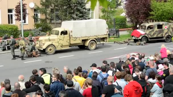 PRAGUE, CZECH REPUBLIC - MAY 2, 2015: reenactment performance battle of World War II on the street - soldiers shooting at each other - retreat of soldiers -  audience (viewer)