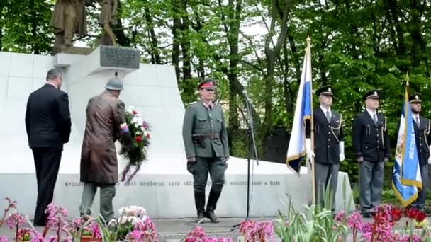 PRAGUE, CZECH REPUBLIC - MAY 2, 2015: commemorate the victims of World War II at the cemetery - official clerk and soldier put down flowers on the grave