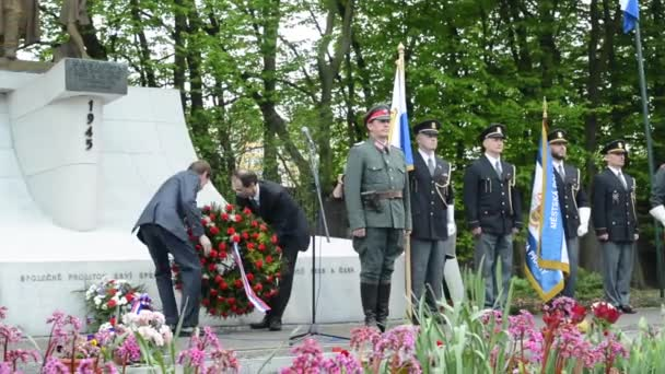 PRAGUE, CZECH REPUBLIC - MAY 2, 2015: commemorate the victims of World War II at the cemetery - official clerks put down flowers on the grave