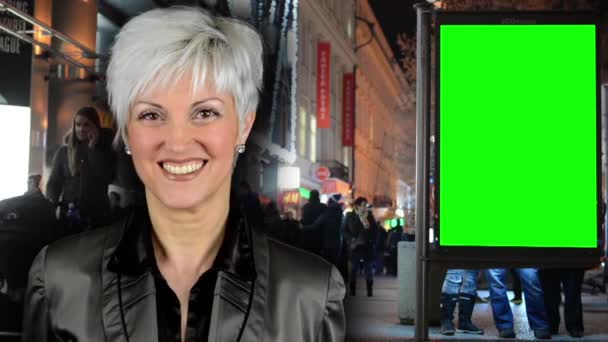 PRAGUE, CZECH REPUBLIC - DECEMBER 2014: business middle aged woman smiles - billboard in the city - urban street with buildings - green screen - walking people - night