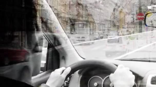 A man drives a car - urban street with passing cars:people - buildings - black and white effect