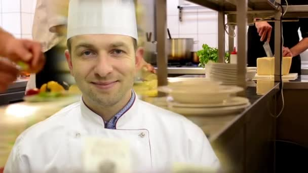 kuchař se usměje na kameramana v kuchyni-restaurace