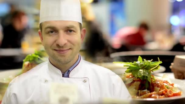 chef smiles to camera - meals (food: pasta) ready for serve