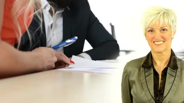 business middle aged woman smiles - man and woman sign a contract in office