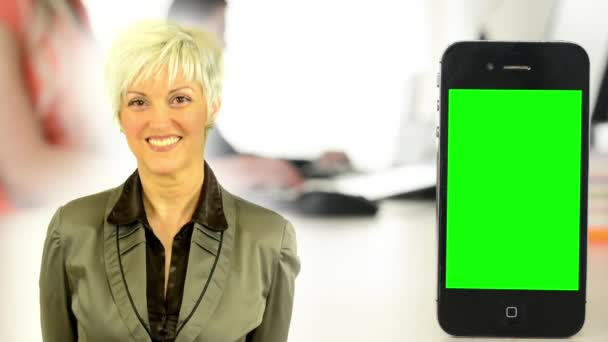 business middle aged woman smiles - smartphone green screen - people working on computers in the office