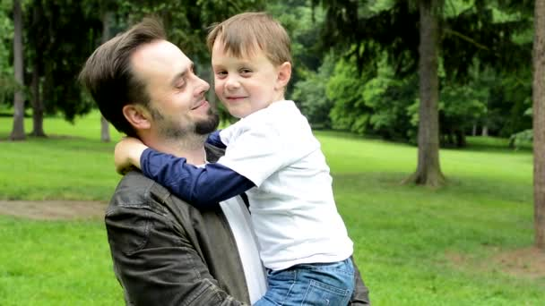 handsome dad with little son smile to camera - park