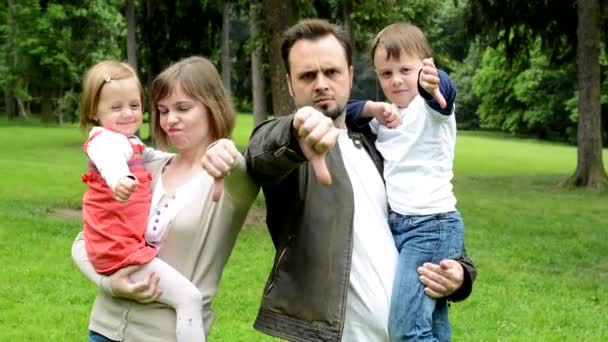 family (middle couple in love, cute girl and small boy) show thumb on disagreement in the park