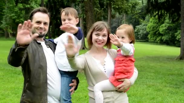 family (middle couple in love, cute girl and small boy) together waving hands in the park