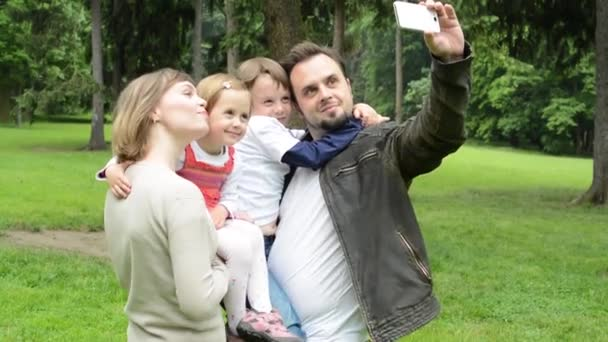 family (middle couple in love, cute girl and small boy) take a photo with smartphone (selfie) - park