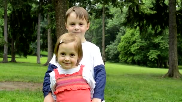 children (siblings - little boy and cute girl) smile to camera - park