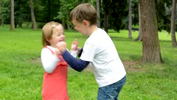 children (siblings - little boy and cute girl) playing in the park (siblings tickle)