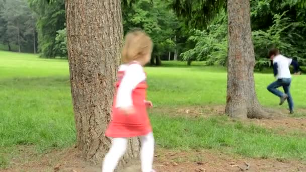 children (siblings - little boy and cute girl) playing in the park (running around trees)