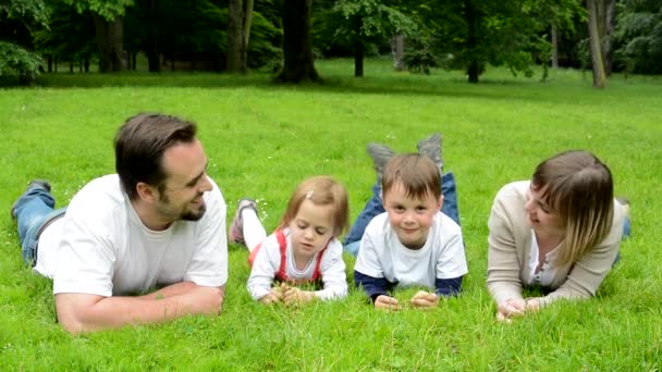 family (middle aged couple in love, boy and girl) lying in grass and smile to camera