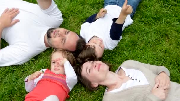 family (middle aged couple in love, boy and girl) lying in grass and talk