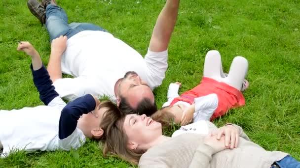 rodina (v lásce, chlapec a dívka středního věku) leží v trávě a mluví