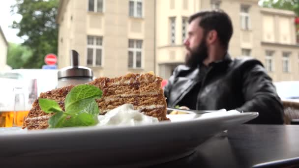 food - dessert - honey cake - young handsome man (hipster) sitting in background - restaurant outdoor seating