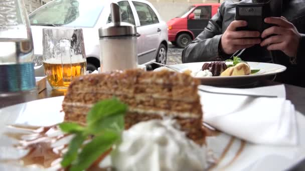 young handsome hipster man photographs food with smartphone (cake) - outdoor seating restaurant