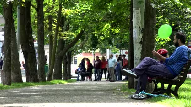 PRAGUE, CZECH REPUBLIC - MAY 31, 2015: people walking in the park and sit on the bench - summer