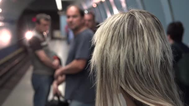 young attractive blonde woman waits for subway and looks around - arriving metro - people enter and leave the subway - woman gets on to metro train unit