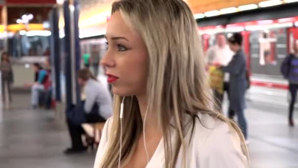 young attractive blonde woman waits in subway and listens music (smartphone) - metro with people in background