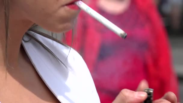 woman smoking a cigarette - urban street with walking people - closeup