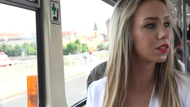young attractive blonde woman traveling by tram and looks out of the window - closeup