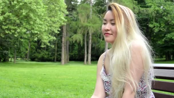 young asian attractive happy woman sits on the bench in the park - look around the park - closeup