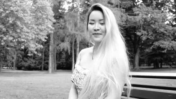 young asian attractive happy woman sits on the bench in the park - smiles to camera - closeup - black and white