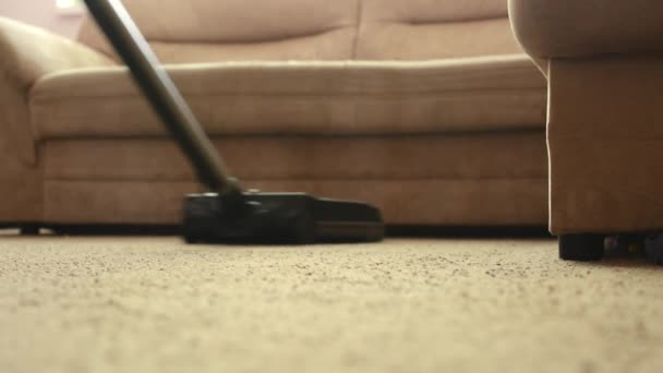 man cleans carpet with vacuum cleaner before couch - close up - detail