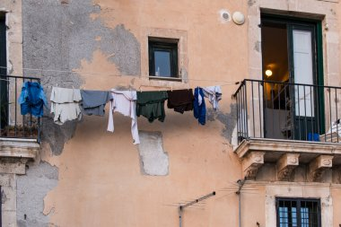 laundry hanging to dry on a wire in front of a wall very spoiled