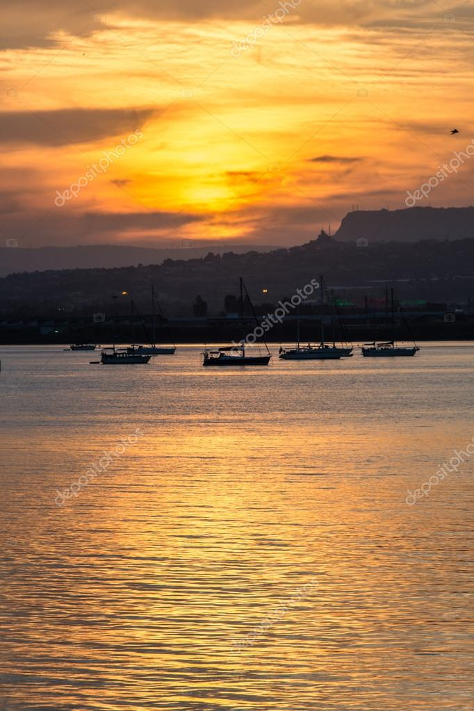 Orange sunset over the sea of Syracuse, Ortigia, Sicily, Italy