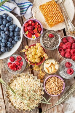 ingredients for a healthy breakfast - berries, fruit and muesli on wooden table, close-up