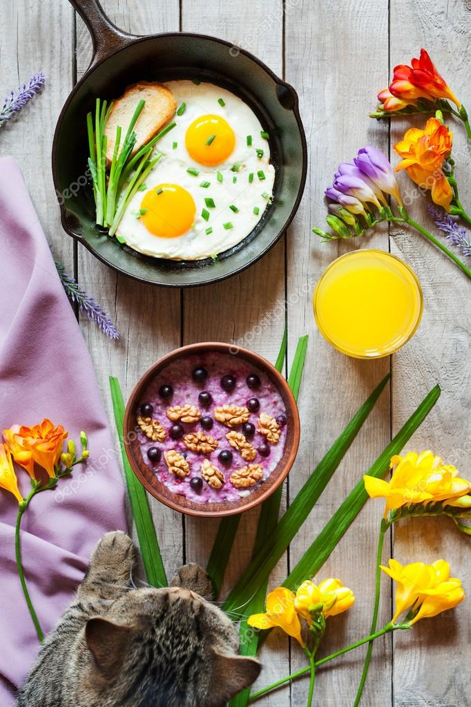 Concept of healthy vegetarian breakfast with flowers and cat
