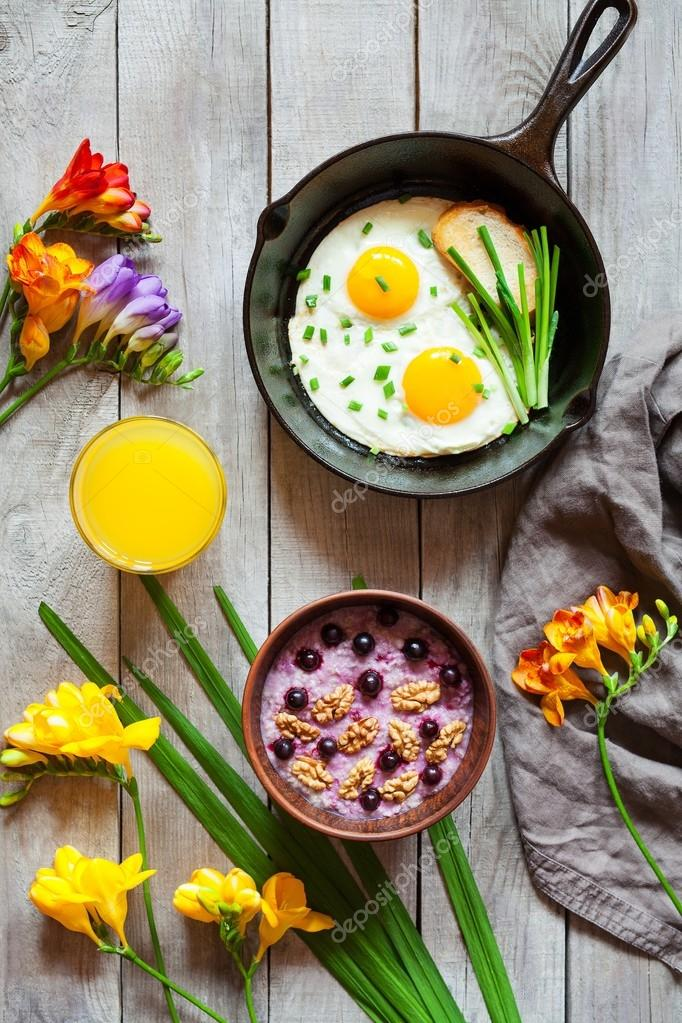 Concept of breakfast with spring mood, oatmeal and fried eggs