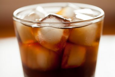 Cola sweet drink with ice cubes and bubbles in glass. Close up shot.