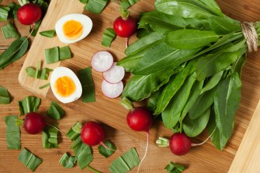 Healthy spring vegetables, sorrel, radish and eggs on wooden table
