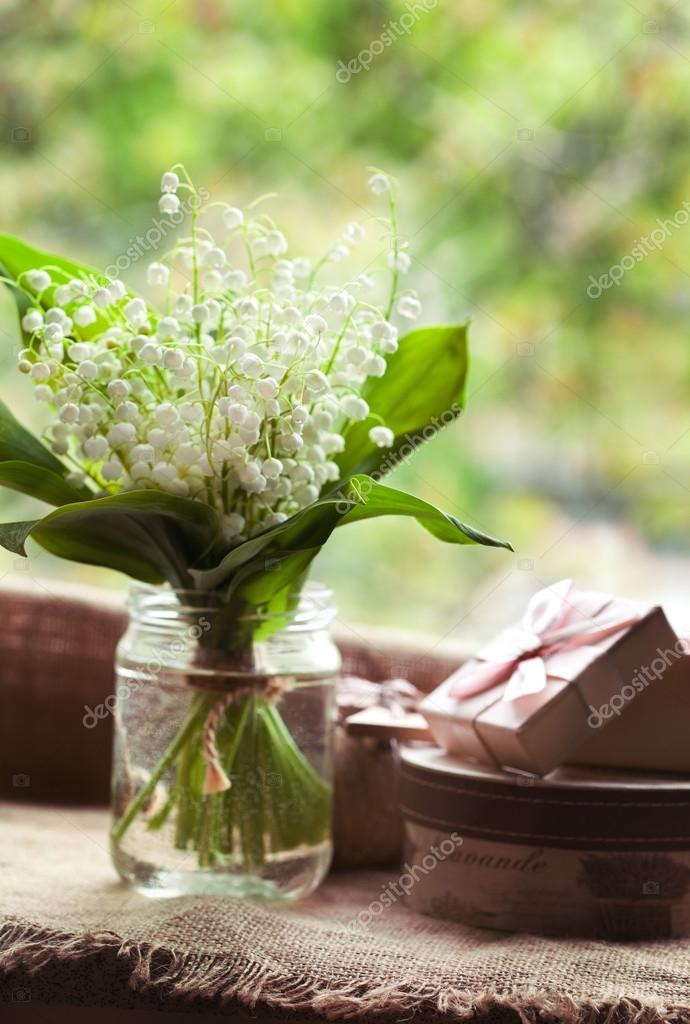Blooming lily of the valley flowers  in glass with water on rustic textile background. Natural light.