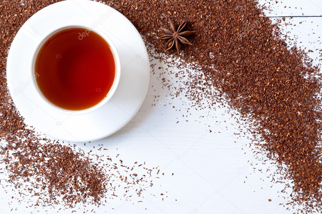 White cup of tasty traditional organic red rooibos tea with star anise