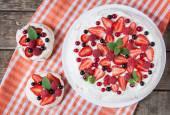Gurmánské domácí tradiční Pavlova sladké desset strana dort se šlehačkou, jahody, blackberry a mátou ponechává o vintage dřevěné pozadí