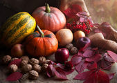 Autumn food design decoration composition with rustic harvest. Pumpkin, nuts, apples, and red leaves on vintage wooden background. Natural light