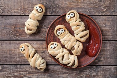 Funny sausage meatball mummies wrapped in dough scary halloween party decoration food on vintage wooden background