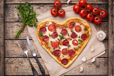 Heart shaped pizza for Valentines day with pepperoni, mozzarella, tomatoes, parsley and garlic on vintage wooden table background. Food symbol of romantic love.