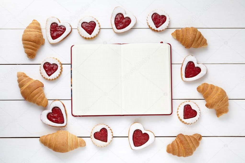 Empty notebook frame for design text, croissants and heart shaped cookies composition on Valentines Day