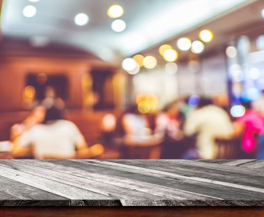 Empty wood table top with restaurant blur with bokeh background