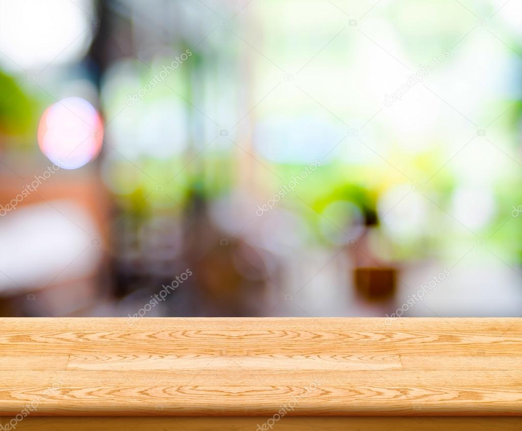 Empty wood table top with coffee shop blur with bokeh background